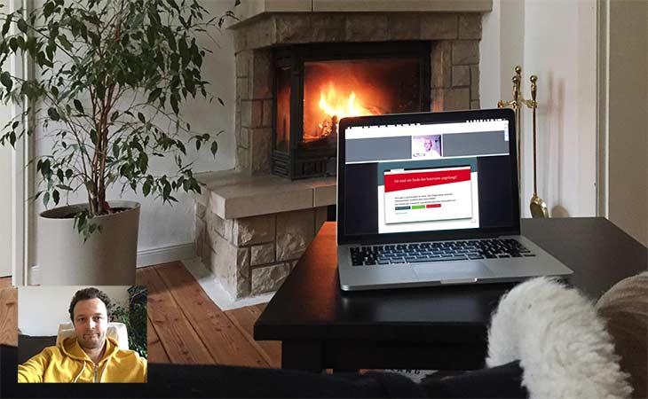 Laptop mit laufendem Webinar vor Kamin